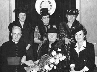 Représentantes de l'exécutif national de la Fédération des femmes canadiennes-françaises en compagnie du chanoine, René Martin, aumônier. Université d'Ottawa, Centre de recherche en civilisation canadienne-française, Fonds Fédération nationale des femmes canadiennes-françaises (C53), Ph 52-1. Photo Lucien Racine, Ottawa, 1945.